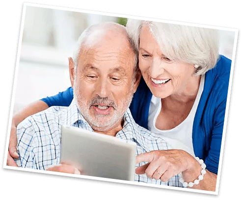 Elderly Couple smiling and hugging while looking at a tablet