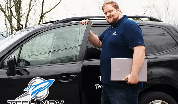 Charlie holding laptop getting into Tech Nav car