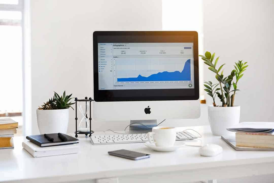 iMac on desk with investment info and coffee cup